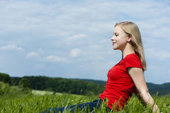 Young girl. Sitting in a meadow royalty free stock image