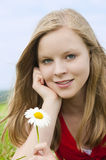 Young girl. With flower on a meadow stock photo