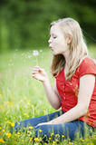 Young girl. With dandelion on a meadow royalty free stock image