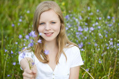Young girl. Sitting in a meadow royalty free stock photography