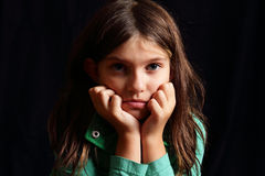 Young girl. A dramatic closeup of a determined dark haired little girl, face resting in her hands with rumpled messy hair. Black background. Shallow depth of Stock Photos