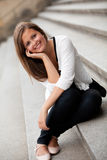 Young girl. Smiling young girl sitting on the steps of Stock Images
