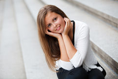 Young girl. Smiling young girl sitting on the steps of Stock Photography