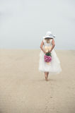 Young Girl. Walking Barefoot on the Beach with Pink Rose Bouquet Royalty Free Stock Photography
