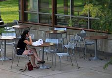 Young girl in abandoned street cafe of University of Minnesota campus. royalty free stock image