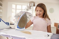 Young girl accidentally burning t shirt with iron royalty free stock image