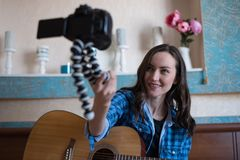 Young girl with acoustic guitar in bedroom records block on DSLR camera while holding it in front of herself on gorillapod.  Royalty Free Stock Photo