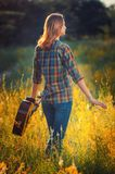 Young girl with an acoustic guitar walks through the autumn fiel Stock Photography