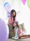 Young girl Adjusting Friend's Tiara On Sofa. Two happy young girls in party costumes with one adjusting other's tiara Stock Photography