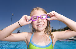 Young girl adjusting goggles next to swimming pool Royalty Free Stock Photo