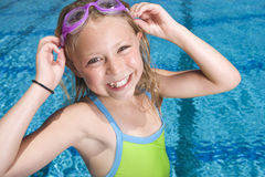 Young girl adjusting goggles next to swimming pool Royalty Free Stock Image