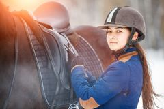 Young girl adjusting stirrups before riding horse. Young girl adjusting stirrups and saddle before riding her bay horse Royalty Free Stock Photography
