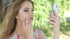 A young girl adjusts her makeup with a phone. A young girl adjusts her makeup with a mobile phone stock photos