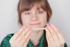 Young girl admires a beads from pearls Royalty Free Stock Photos