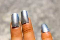 Silver nails to fascinate and amaze. Young girl admires her new silver artificial nails stock photo