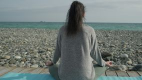 Back view of young woman meditating near sea shore stock footage