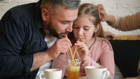 Young girl of adolescence along with her dad have fun at the cafe. They are drinking crimson juice with ice through a. Tube and laughing. HD, fathers day, good stock footage