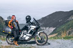 Young girl with adventure motorcycle. woman rider. Top of the mountain road. Motorbike vacation. Travel and active lifestyle royalty free stock image