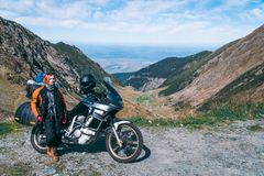 Young girl with adventure motorcycle. woman rider. Top of the mountain road. Motorbike vacation. Travel and active lifestyle stock image