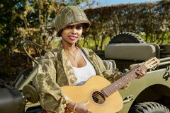 Young girl african american with military uniform and guitar Royalty Free Stock Images