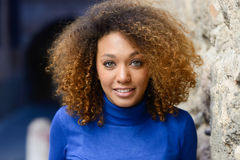 Young girl with afro hairstyle smiling in urban background Stock Photo