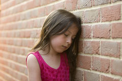 Young girl against a brick wall Royalty Free Stock Images
