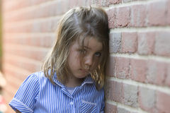 Young girl against a brick wall Stock Photo