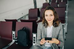 Girl sitting at the airport, holding smartphone royalty free stock photo