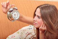 Young girl and alarm clock Stock Images