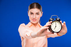 Young girl with an alarm clock in focus Stock Images