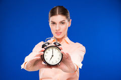 Young girl with an alarm clock in focus Stock Image