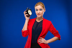Young girl with an alarm clock in hands. On a blue background Royalty Free Stock Photo