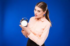 Young girl with an alarm clock in hands. On a blue background Royalty Free Stock Images