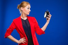 Young girl with an alarm clock in hands. On a blue background Stock Photos