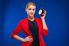Young girl with an alarm clock in hands. On a blue background Royalty Free Stock Image