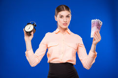Young girl with an alarm clock and money Royalty Free Stock Photos