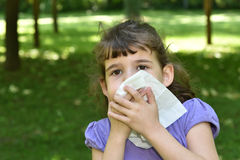 Young girl with allergy symptom. Blowing her nose Stock Photo