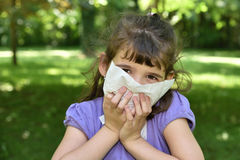 Young girl with allergy symptom. Sneezing in a tissue Royalty Free Stock Photo