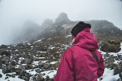 A young girl alone in the caucasian mountains looks at the rocks at the foot of which lies the snow. Rocks envelop misty Stock Image