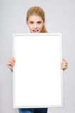 Young girl amazed holding in front a white blank board. Stock Images