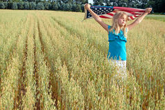 Young girl with American flag in field Royalty Free Stock Image