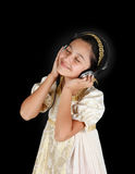 Young girl in ancient dress while listening music with headphone Stock Photo