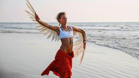 Young girl with angel wings dancing on the beach at sunset stock image