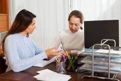 Young girl answering questions of with laptop employee. At office royalty free stock image