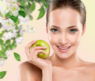 Young girl with apple. Young girl smiling holding a green Apple. Health & beauty royalty free stock images