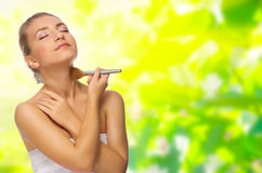 Young girl applying face powder on spring background Royalty Free Stock Photos