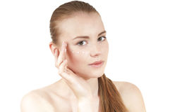 Young girl  applying moisturizer cream on her face. Royalty Free Stock Image