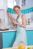 A young girl in an apron prepares food Stock Photography