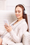 Young girl in the armchair listening to music. Feel the music. Young girl is resting in the armchair and listening to music with her headphones Stock Photos