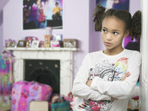 Young Girl With Arms Crossed Showing Attitude. Young girl leaning against door with arms crossed and showing attitude Stock Image